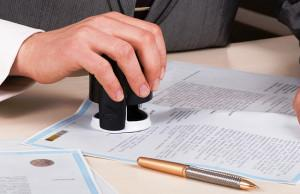 A person at a desk using a stamp or corporate seal on documents